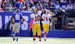 Washington Redskins quarterback Robert Griffin III (10) points to the sky after throwing touchdown to Santana Moss in the second quarter at MetLife Stadium, East Rutherford, N.J., Oct. 21, 2012. (Preston Keres/Special to The Washington Times)