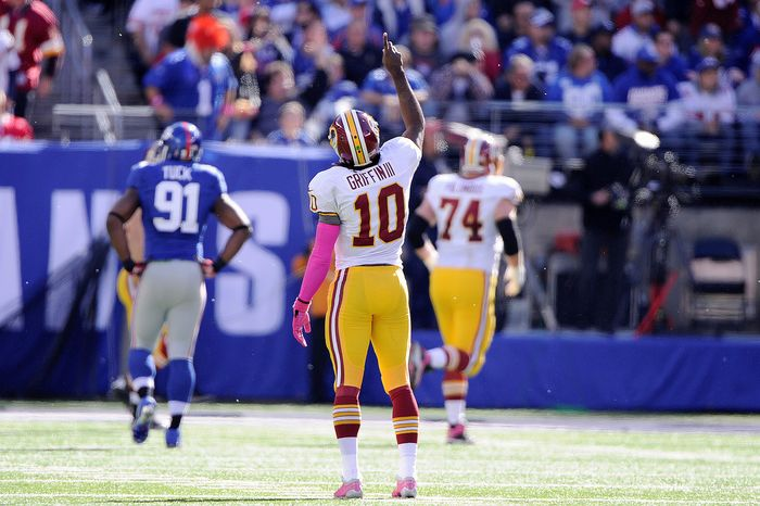 Washington Redskins quarterback Robert Griffin III (10) points to the sky after throwing touchdown to Santana Moss in the second quarter at MetLi