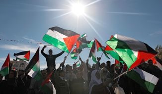Palestinians wave flags as they celebrate their successful bid to win U.N. statehood recognition on Sunday. Israel said it would withhold more than $100 million collected for the Palestinian government to pay debts to Israeli companies. (Associated Press)