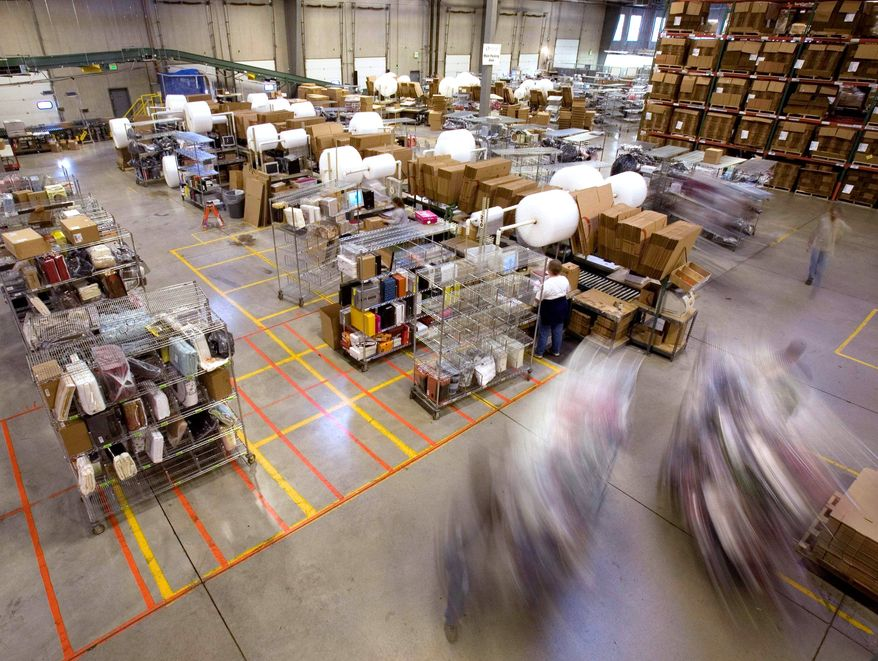 **FILE** Carts full of merchandise ordered on the Internet are rolled to the main packing area for shipping at an Overstock.com warehouse in Salt Lake City. (Associated Press)