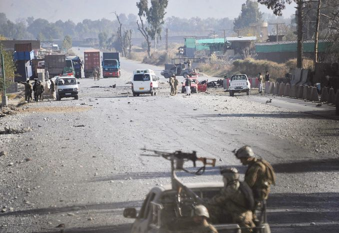 Afghan security forces block the road where Taliban suicide bombers attacked a joint U.S.-Afghan air base in Jalalabad, east of Kabul, Afghanistan, on Sunday, Dec. 2, 2012. The suicide bombers detonated explosives at the gate, and sparking