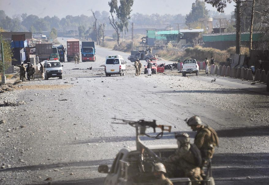 Afghan security forces block the road where Taliban suicide bombers attacked a joint U.S.-Afghan air base in Jalalabad, east of Kabul, Afghanistan, on Sunday, Dec. 2, 2012. The suicide bombers detonated explosives at the gate, and sparking a gunbattle that lasted at least two hours, with American helicopters firing down at militants before the attackers were defeated. (AP Photo/Nasrullah Khan)