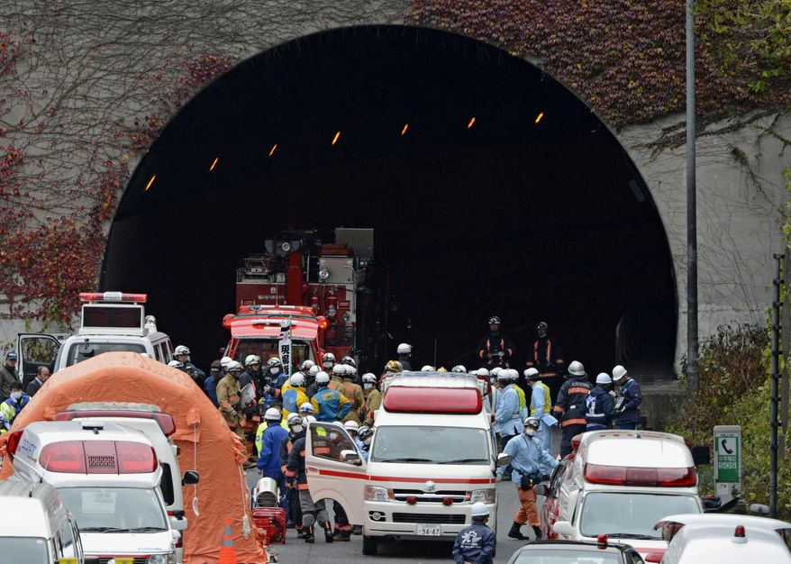 Police officers and firefighters gather at the entrance to the Sasago Tunnel on the Chuo Expressway in Otsuki, Yamanashi Prefecture, in central Japan, on Sunday, Dec. 2, 2012. Parts of the tunnel collapsed, trapping an unknown number of vehicles, as smoke from a fire inside prevented rescuers from approaching. (AP Photo/Kyodo News)