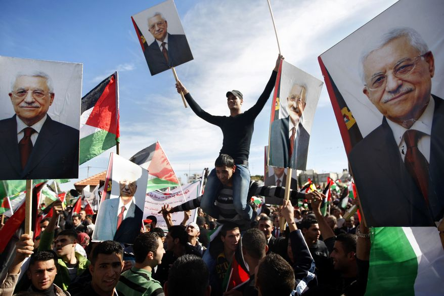 Palestinians hold pictures of Palestinian President Mahmoud Abbas as they celebrate their successful bid to win U.N. observer recognition, in the West Bank city of Ramallah on Sunday, Dec. 2, 2012. (AP Photo/Majdi Mohammed)