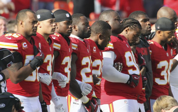 Kansas City Chiefs players stand arm in arm during a moment of silence for victims of violence before an NFL football game against the Carolina Panthers at Arrowhead Stadium in Kansas City, Mo., on Sunday, Dec. 2, 2012. (AP Photo/Colin E. Braley)