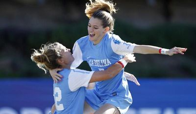 North Carolina's Kealia Ohai leaps into the arms of teammate Amber Brooks after Ohai scored a goal against Penn State in the first half of the NCAA women's College Cup final soccer game in San Diego on Sunday, Dec. 2, 2012. (AP Photo/U-T San Diego, Hayne Palmour IV) SAN DIEGO COUNTY OUT; NO SALES; COMMERCIAL INTERNET OUT; FOREIGN OUT.