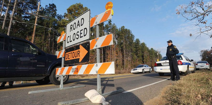 Highway 163 just south of Doyline, La., is blocked Saturday as authorities begin moving up to 6 million pounds of improperly stored explosive powder from Doyline to storage bunkers at a state-owned site. State police have opened a criminal investigation. (ShreveportTimes.com via Associated Press)
