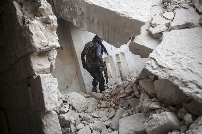 **FILE** A rebel fighter walks Nov. 2, 2012, among the debris of damaged residential buildings after several days of intense fighting between rebel fighters and the Syrian army in the Karm al-Jebel neighborhood in Aleppo, Syria. (Associated Press)