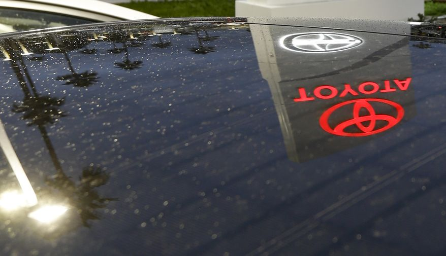 A Toyota dealership sign glows over a car lot in Tustin, Calif., on Thursday, Nov. 8, 2012. (AP Photo/Chris Carlson)