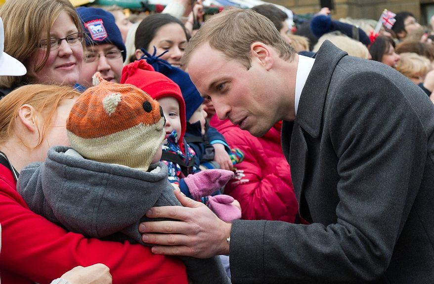 **FILE** Britain's Prince William meets Nov. 28, 2012, with a young member of the public as she arrives at the Guildhall during a visit to Cambridge, England. (Associated Press)