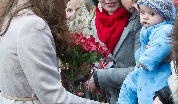 **FILE** Britain's Kate Duchess of Cambridge (left) meets Nov. 28, 2012, with a young member of the public as she arrives at the Guildhall during a visit to Cambridge, England. (Associated Press)