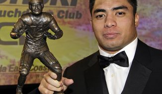 Notre Dame linebacker Manti Te'o poses with the Bronko Nagurski Trophy during a news conference in Charlotte, N.C., Monday, Dec. 3, 2012. The award is given annually to the national collegiate defensive player of the year. (AP Photo/Chuck Burton)