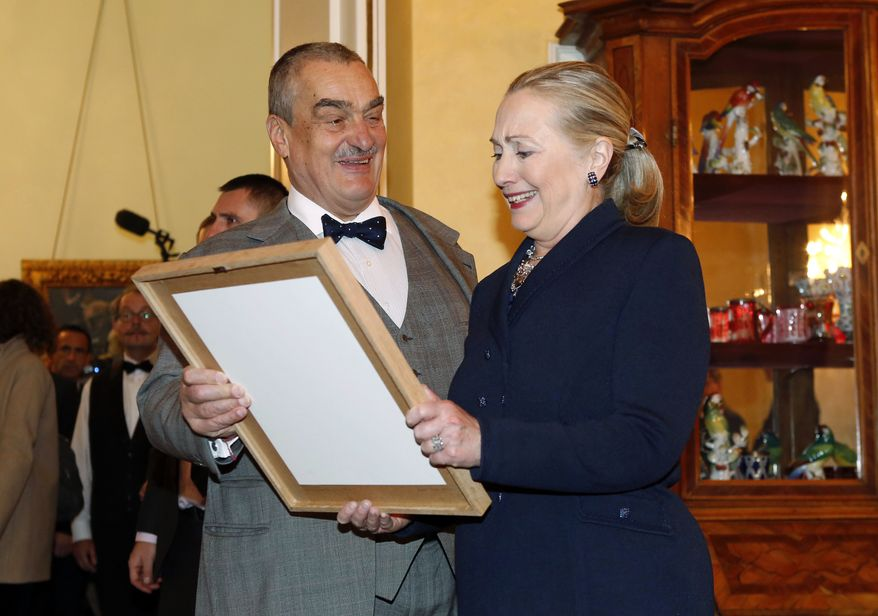 U.S. Secretary of State Hillary Rodham Clinton (right) receives a photo of herself with her husband, former President Bill Clinton, and former Czech President Vaclav Havel, presented by Czech Foreign Minister Karel Schwarzenberg, at the Foreign Ministry in Prague on Monday, Dec. 3, 2012. Mrs. Clinton is on a six-day trip to Europe. (AP Photo/Kevin Lamarque)