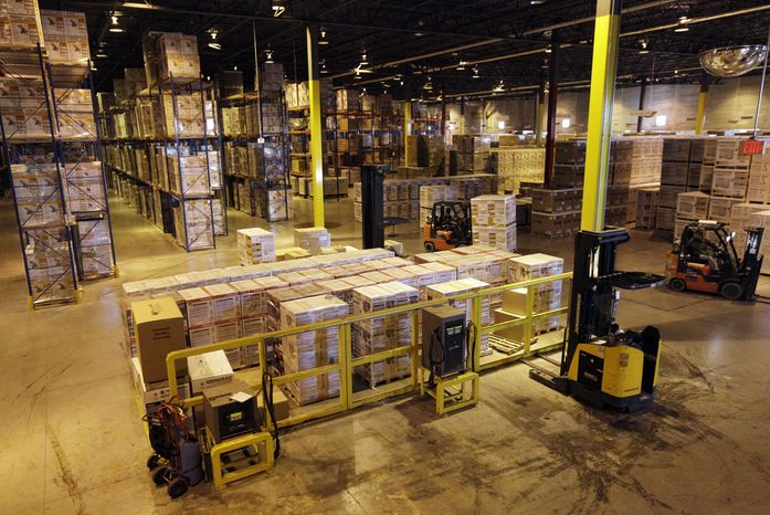 Employees work in a shipping area of Generac Power Systems Inc., one of the nation's largest makers of residential generators, in Whitewater, Wis., on Friday, Nov. 16, 2012. (AP Photo/Nam Y. Huh)