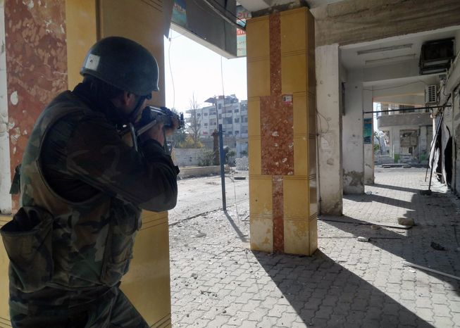 A Syrian soldier aims his rifle at free Syrian Army fighters during clashes in the Damascus suburb of Daraya, Syria, on Dec. 2, 2012. (Associated Press/SANA)