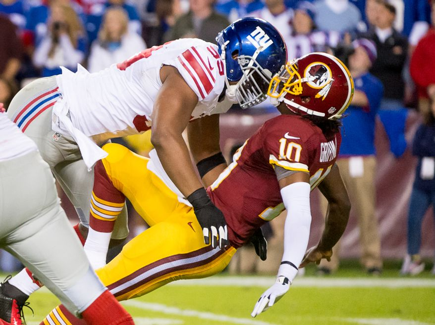 Washington Redskins quarterback Robert Griffin III (10) is hit by New York Giants defensive tackle Chris Canty (99) as he completes a 25 yard pass to Washington Redskins wide receiver Pierre Garcon (88) in the first quarter as the Washington Redskins play the New York Giants for monday night football at FedEx Field, Landover, Md., Monday, December 3, 2012. (Andrew Harnik/The Washington Times)