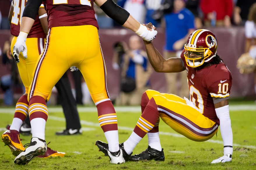 Washington Redskins quarterback Robert Griffin III (10) helped to his feet after being hit by New York Giants defensive tackle Chris Canty (99) in the first quarter as the Washington Redskins play the New York Giants for monday night football at FedEx Field, Landover, Md., Monday, December 3, 2012. (Andrew Harnik/The Washington Times)