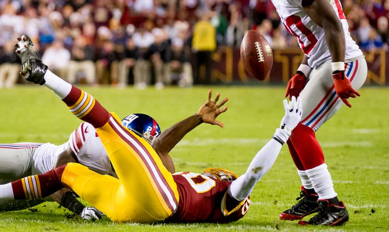 Washington Redskins quarterback Robert Griffin III (10) fumbles after scrambling for a 12 yard gain in the first quarter as the Washington Redskins play the New York Giants for monday night football at FedEx Field, Landover, Md., Monday, December 3, 2012. The ball was recovered by Washington Redskins w