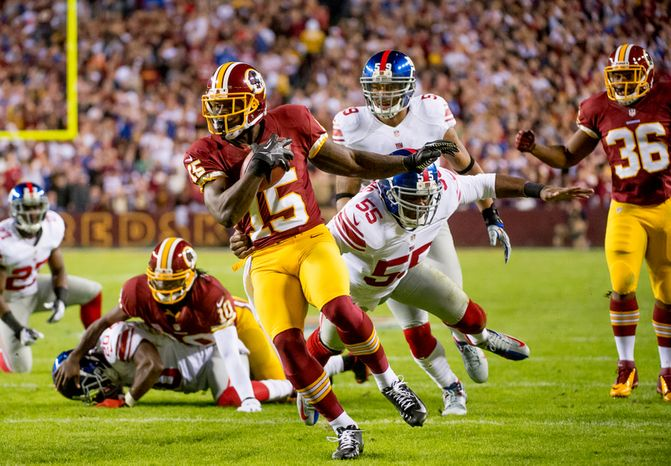 Washington Redskins wide receiver Josh Morgan (15) scores on a 13 yard run after picking up a fumble by Washington Redskins quarterback Robert Griffin III (10) to put the Redskins up 7-3 in the first quarter as the Washington Redskins play the New York Giants for monday night football at FedEx Field, Landover, Md., Monday, December 3, 2012. (Andrew Harnik/The Washington Times)