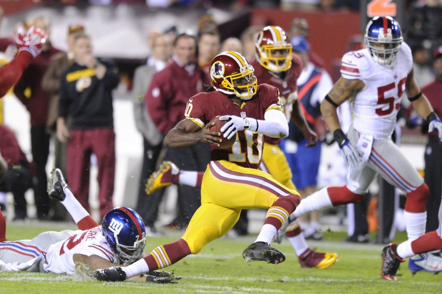 Washington Redskins quarterback Robert Griffin III (10) runs through the Giants defense for 12 yards before fumbling in the first quarter. The ball was picked up by wide receiver Josh Morgan (15) and run in for the Redskins' first touchdown of the night at FedEx Field, Landover, Md., Dec. 3, 2012. (Preston Keres/Special to The Washington Times)