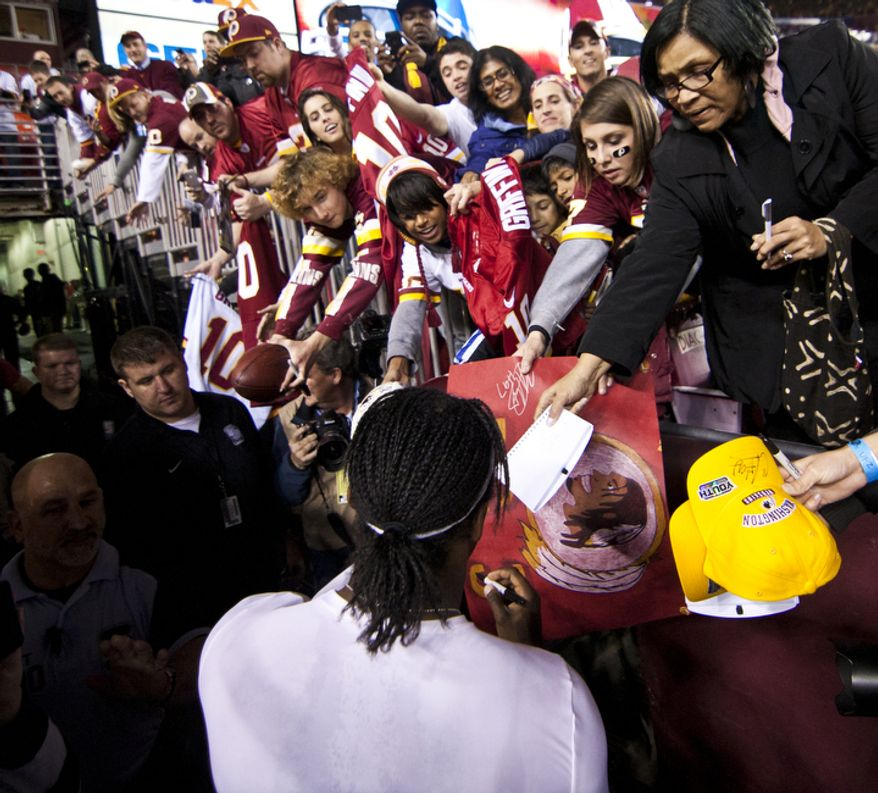 Washington Redskins quarterback Robert Griffin III (10) signs autographs before playing host to the New York Giants on Monday Night Football at FedEx Field, Landover, Md., Monday, December 3, 2012.  (Craig Bisacre/The Washington Times)