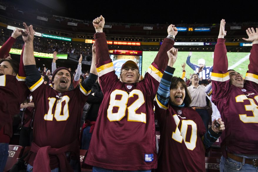 Pat Romano, 49, left, from Manassas Va., Ira Golagold, 65, center, and wife Linda Golagold, right, from Potomac, Md., react to a booth review of Washington Redskins quarterback Robert Griffin III (10) fumble which was recovered by wide receiver Josh Morgan (15) for the Redskins first touchdown against the New York Giants, Landover, Md., Monday, December 3, 2012.  (Craig Bisacre/The Washington Times)
