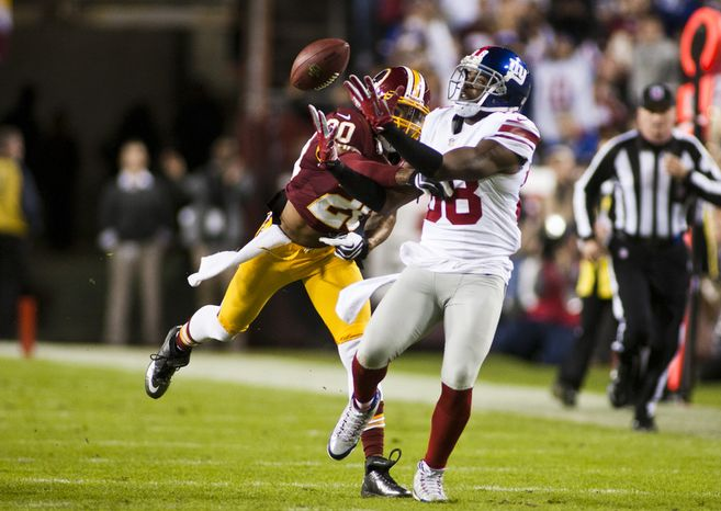Washington Redskins defensive back Cedric Griffin (20) breaks up a pass intended for New York Giants wide receiver Hakeem Nicks (88) in the first quarter, Landover, Md., Monday, December 3, 2012.  (Craig Bisacre/The Washington Times)
