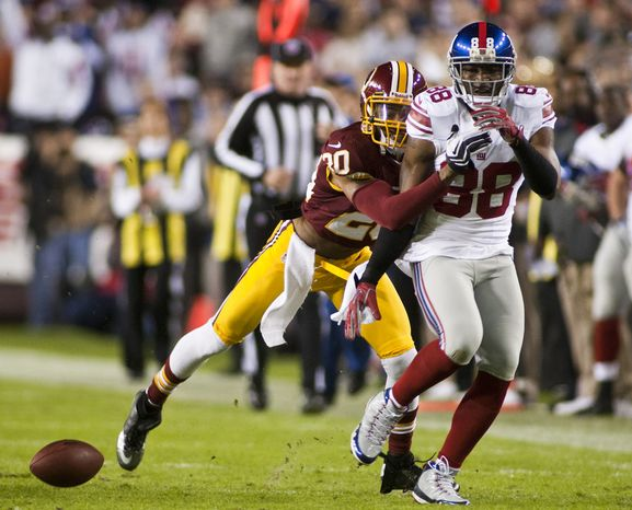 Washington Redskins defensive back Cedric Griffin (20) breaks up a pass intended for New York Giants wide receiver Hakeem Nicks (88) in the first quarter, Landover, Md.,