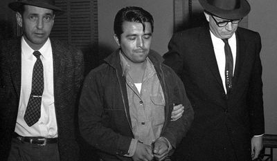 Perry Smith (center) is escorted into the Garden City, Kan., courthouse in 1960. Smith and Richard Hickock were executed for killing four members of a Kansas family. Now authorities want to check their DNA in connection with the 1959 unsolved slaying of a family of four in Florida. (Associated Press)