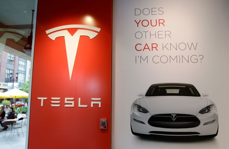 **FILE** A sign is shown inside of electric car maker Tesla Motors showroom in San Jose, Calif., on May 25, 2011. (Associated Press)