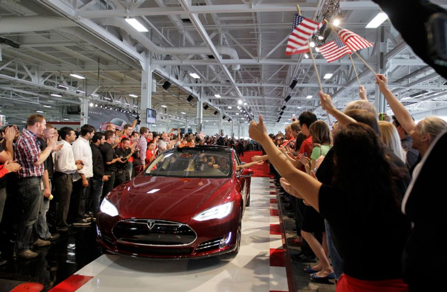 **FILE** Tesla workers cheer on the first Tesla Model S cars sold during a rally at the Tesla factory in Fremont, Calif., on June 22, 2012. (Associated Press)
