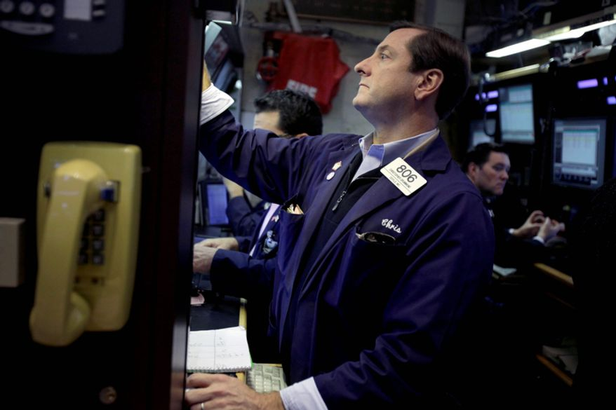 **FILE** Traders work on the floor at the New York Stock Exchange in New York on Nov. 15, 2012. (Associated Press)