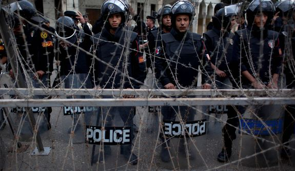 Egyptian riot police stand guard Dec. 4, 2012, behind barbed wire in front of the presidential palace in Cairo while protesters chant slogans against the Muslim Brotherhood during a demonstration. (Associated Press)