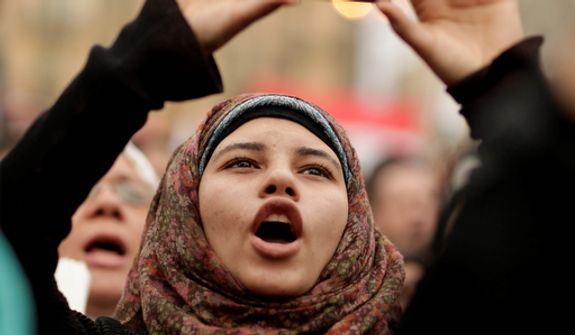An Egyptian protester takes a photo with her mobile phone as she chants slogans in Tahrir Square in Cairo on Dec. 4, 2012. Hundreds of black-clad riot police deployed around the Itihadiya palace in Cairo's district of Heliopolis. (Associated Press)