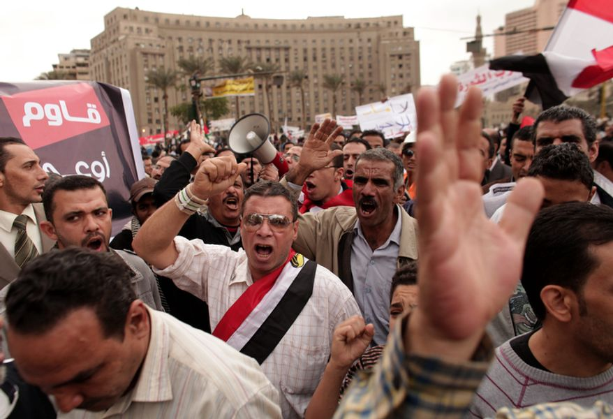 Protesters chant slogans and wave Egyptian national flags in Tahrir Square in Cairo on Dec. 4, 2012. Hundreds of black-clad riot police deployed around the Itihadiya palace in Cairo's district of Heliopolis. (Associated Press)