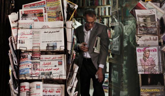 An Egyptian walks past a stand displaying state-owned newspapers in Cairo on Dec. 4, 2012. Most independent Egyptian newspapers suspended publication of that day's edition in protest over the hurried drafting of the country's new constitution adopted by an Islamist-led panel. (Associated Press)