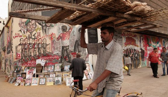 A bread vendor balances his wares on his head Dec. 4, 2012, while passing a mural and photographs depicting protesters killed in the unrest in Egypt. (Associated Press)