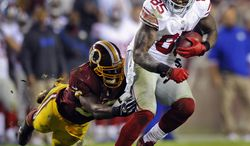 Washington Redskins inside linebacker London Fletcher reaches to stop New York Giants tight end Martellus Bennett (85) during the first half of an NFL football game in Landover, Md., Monday, Dec. 3, 2012. (AP Photo/Nick Wass)