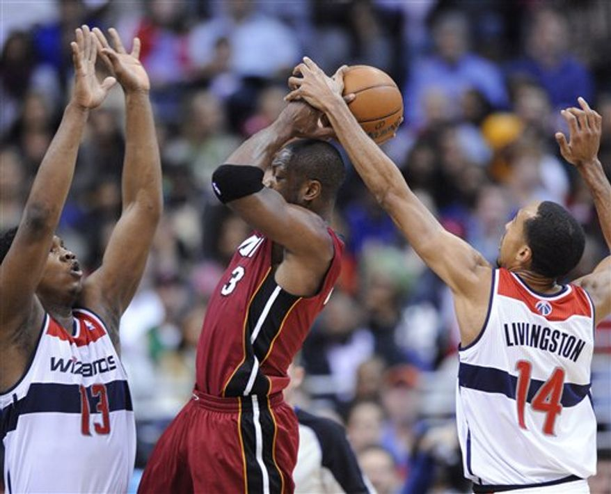 Washington Wizards' Kevin Seraphin (13) and Shaun Livingston (14) defend Miami Heat guard Dwyane Wade (3) during the second half of an NBA game, Tuesday, Dec. 4, 2012, in Washington. The Wizards won 105-101. (AP Photo/Nick Wass)
