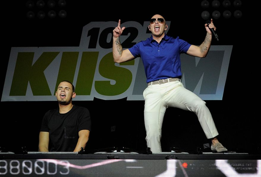 Afrojack, left, is joined by surprise guest Pitbull during his set on the second night of KIIS FM's Jingle Ball at Nokia Theatre LA Live on Monday, Dec. 3, 2012, in Los Angeles. (Photo by Chris Pizzello/Invision/AP)