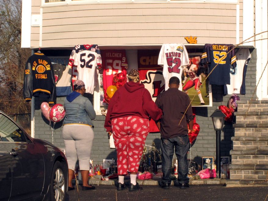 People stand by a small shrine outside the Long Island home of Kansas City Chiefs linebacker Jovan Belcher on Dec. 3, 2012, in West Babylon, N.Y. People living at and visiting the home stopped and recited a prayer at the shrine. Two days earlier, Belcher killed his girlfriend and himself in Kansas City, Mo. (Associated Press)