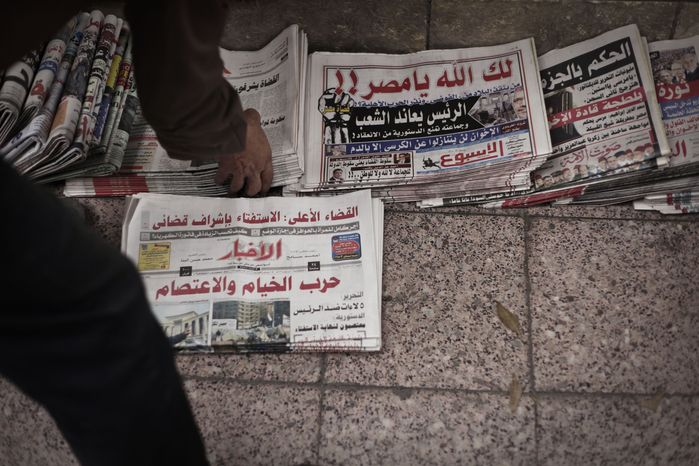 An Egyptian news vendor arranges state-owned newspapers for sale on the street in Cairo on Tuesday, Dec. 4, 2012. Most independent Egyptian newspapers suspended publication of Tuesday's edition in protest over the hurried drafting of the country's new constitution adopted by an Islamist-led panel. (AP Photo/Nariman El-Mofty)