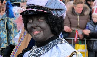 A person dressed as Zwarte Piet, or Black Pete, attends a parade after Sinterklaas, as the Dutch call Santa Claus, arrived by boat in Amsterdam on Sunday, Nov. 18, 2012. (AP Photo/Margriet Faber)