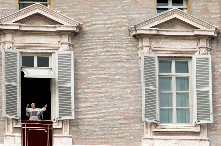 Pope Benedict XVI waves to the faithful during the Angelus prayer he delivered from his studio window overlooking St. Peter's Square at the Vatican on Sunday, Dec. 2, 2012. (AP Photo/Gregorio Borgia)