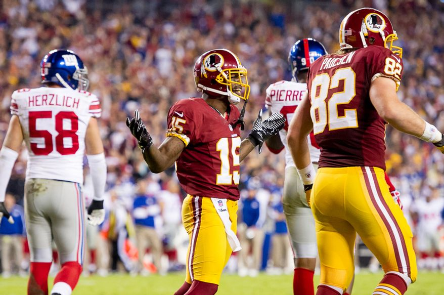 Washington Redskins wide receiver Josh Morgan (15) shrugs after scoring on a 13-yard run off of a fumble by quarterback Robert Griffin III (10) to put the Redskins up 7-3 in the first quarter as the Redskins play the New York Giants on Monday Night Football at FedEx Field, Landover, Md., December 3, 2012. (Andrew Harnik/The Washington Times)