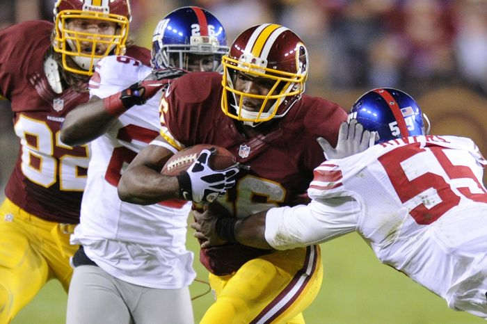 Washington Redskins running back Alfred Morris (46) runs for an 8-yard gain against New York Giants outside linebacker Keith Rivers (55) and free safety Antrel Rolle (26) in the first quarter at FedEx