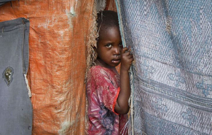 **FILE** A Somali internally-displaced child looks out from her family's makeshift home in Maslah camp on the outskirts of Mogadishu, Somalia, on Nov. 29, 2012. (Associated