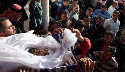 Syrians and Jordanians carry the body of Moath al-Rawashdy, 30 years, who was killed from Syrian government forces shelling during his funeral procession in Ramtha City, north Amman, Jordan, Sunday, Dec. 2, 2012. Al-Rawashdy was killed in Tafas village, in the Syrian city of Daraa, on Dec. 1, 2012. (AP Photo/Mohammad Hannon)