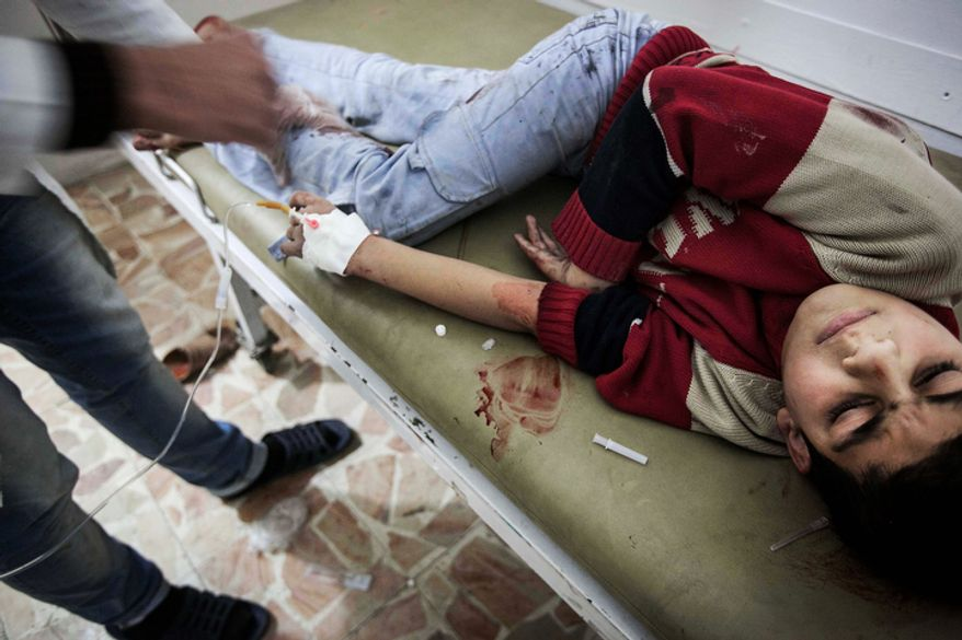 A boy injured by shrapnel receives treatment in a makeshift clinic during heavy fighting between Free Syrian Army fighters and government forces in Aleppo, Syria, on Sunday, Dec. 2, 2012. (AP Photo/Narciso Contreras)