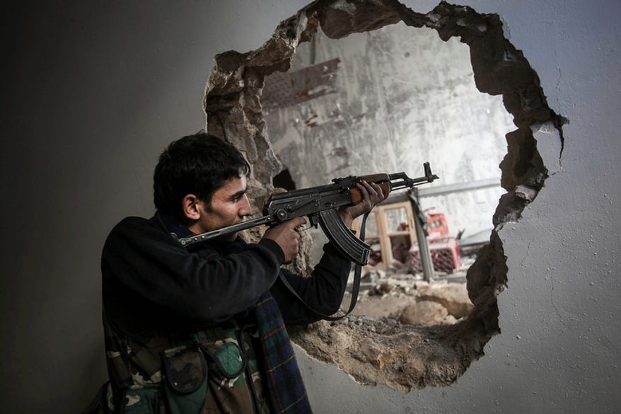 A Free Syrian Army fighter aims his weapon during clashes with government forces in Aleppo, Syria, on Sunday, Dec. 2, 2012. (AP Photo/Narciso Contreras)